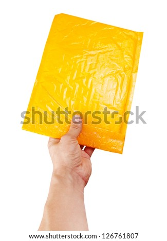 Hand holding yellow mail package, isolated on white - stock photo