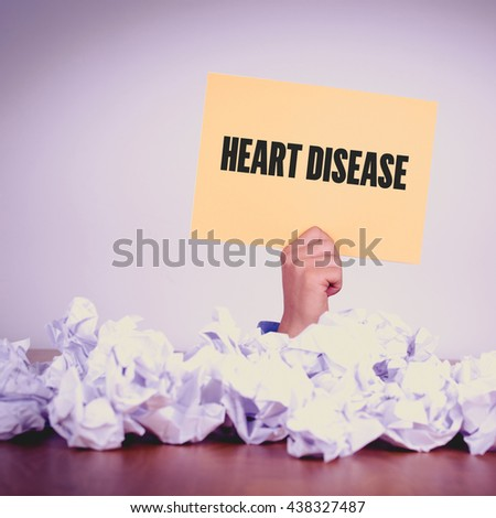 HAND HOLDING YELLOW PAPER WITH HEART DISEASE CONCEPT - stock photo