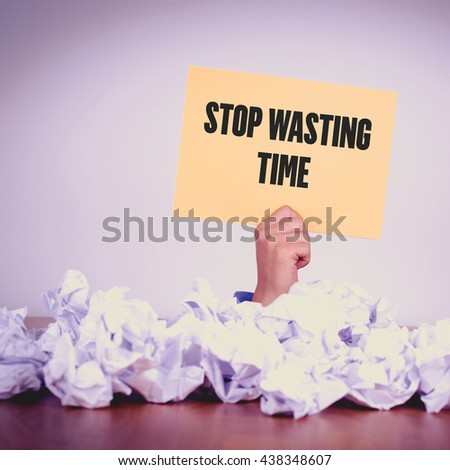 HAND HOLDING YELLOW PAPER WITH STOP WASTING TIMECONCEPT - stock photo