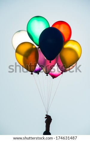 hand holds a bunch of balloons - stock photo