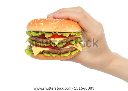 Hand holds big hamburger on white background close-up  - stock photo