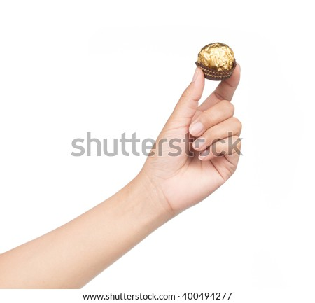 Hand holds Chocolate balls with almond in gold foil paper isolated on white background - stock photo