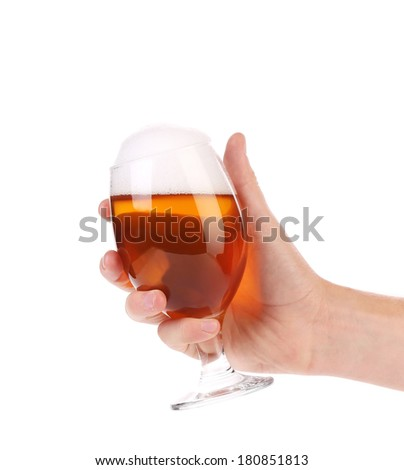 Hand holds glass of beer. Isolated on a white background. - stock photo