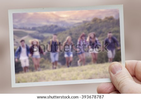 hand holds snapshot of group of hikers in the mountain running holding hands - stock photo