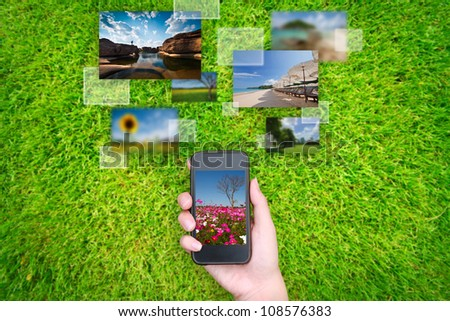hand holds touch screen mobile phone streaming images on grass - stock photo
