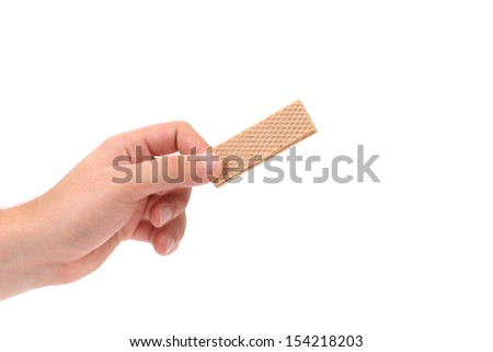 Hand holds wafer of chocolate. Isolated on a white background. - stock photo