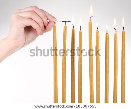 Hand ignites candles isolated on white - stock photo