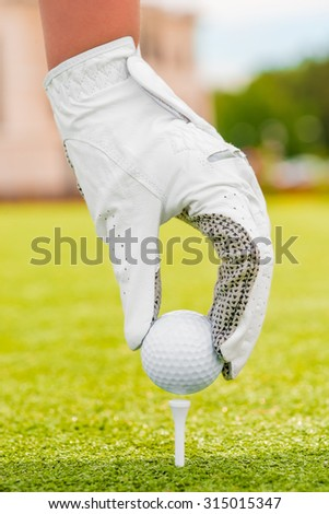 Hand in a white glove puts the golf ball on a tee - stock photo