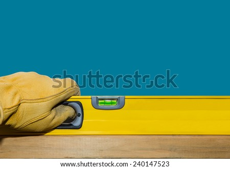 Hand in a work glove holding a level on edge of wood to determine if it is level.  - stock photo