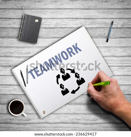 Hand in an office environment drawing about teamwork - stock photo