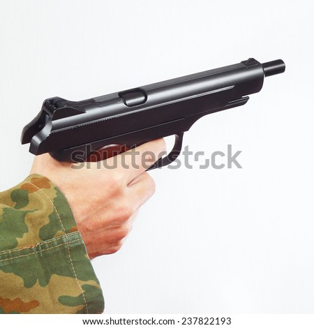 Hand in camouflage uniform with discharged handgun on a white background - stock photo