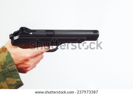 Hand in camouflage uniform with handgun on a white background - stock photo