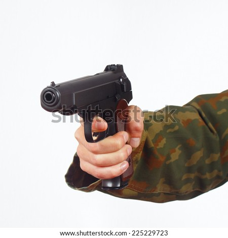 Hand in camouflage uniform with pistol on a white background - stock photo