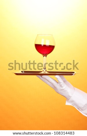 Hand in glove holding silver tray with wineglass on yellow background - stock photo