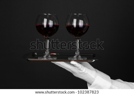 Hand in glove holding silver tray with wineglasses isolated on black - stock photo