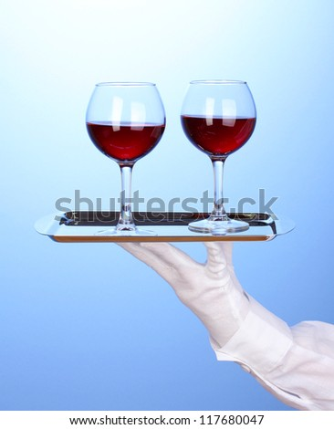 Hand in glove holding silver tray with wineglasses on blue background - stock photo