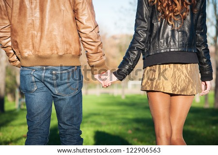 Hand in hand romantic young couple walking outdoors in autumn park. - stock photo