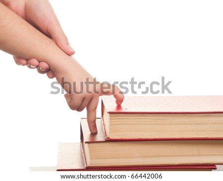 hand in hand, the adult helps the child to walk up the steps of the books - stock photo