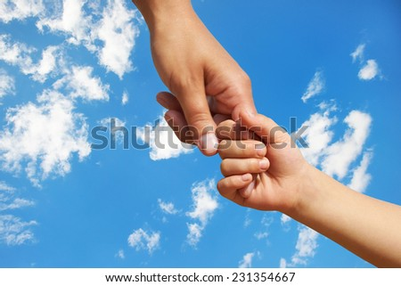 Hand in hand the child the mother against the blue sky - stock photo