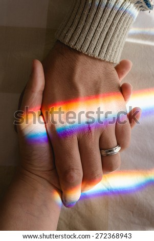 hand in hand with rainbow symbolizing endless bond - stock photo