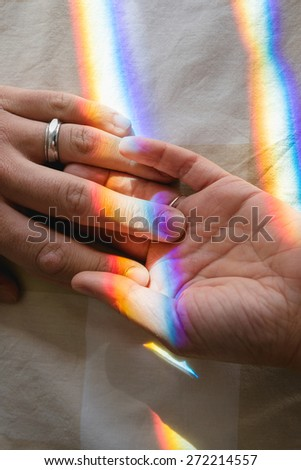 hand in hand with rainbow symbolizing human bond - stock photo
