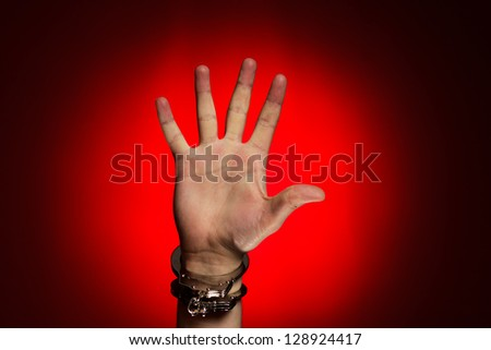 hand in handcuffs over red background concept - stock photo