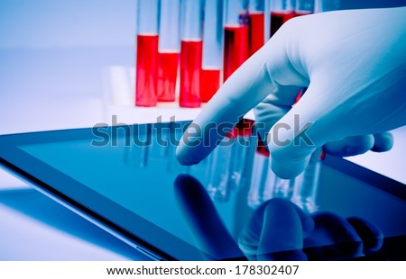 hand in medical blue glove touching modern digital tablet in laboratory. Concept of medical or research theme - stock photo