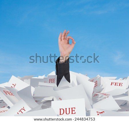 hand in papers heap showing ok symbol - stock photo