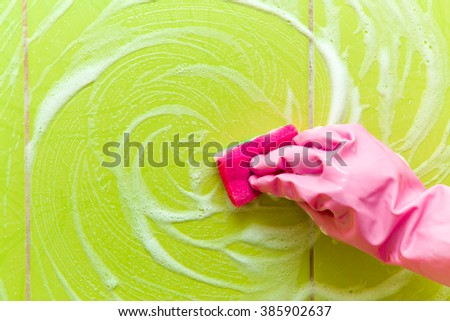 Hand in pink protective glove cleaning tiles with sponge. Early spring cleaning or regular clean up. Maid cleans house. - stock photo