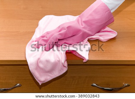 Hand in pink protective glove cleaning wooden furniture with rag. Early spring cleaning or regular clean up. Maid cleans house. - stock photo