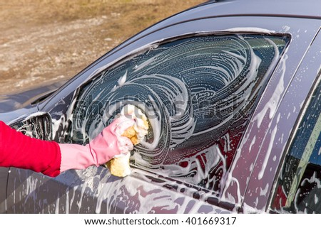 Hand in pink protective glove washing a cars window with sponge. Early spring washing or regular wash up. Professional car wash by hands. - stock photo