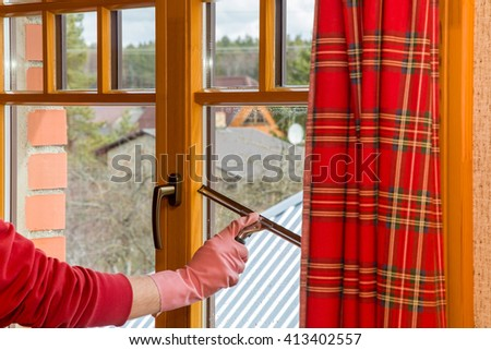 Hand in pink protective glove washing and cleaning window with professionally squeegee. Early spring windows cleaning. Maid cleans window. - stock photo
