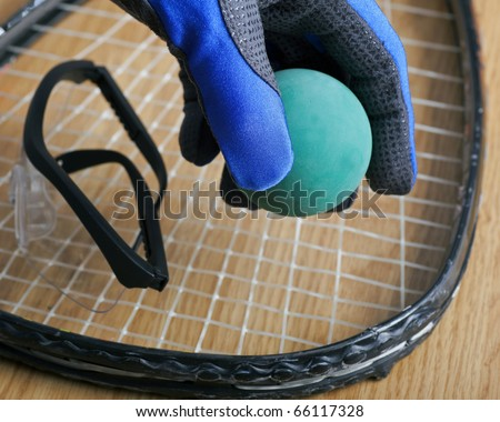 Hand in racquetball glove picking up ball. - stock photo