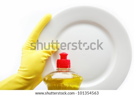 Hand in rubber glove with a plate and a bottle of detergent on a white background. - stock photo