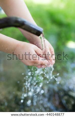 hand in tap water in nature - stock photo
