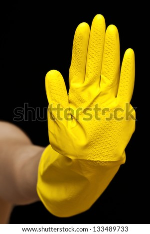 Hand in yellow glove isolated on black background. Concept of cleaning - stock photo