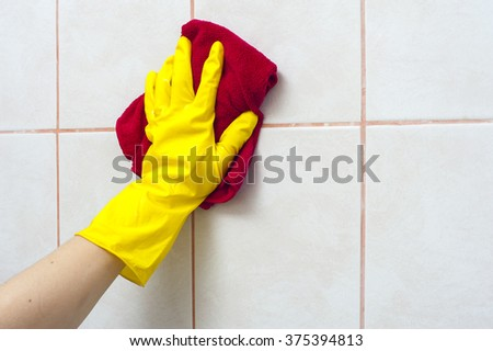 Hand in yellow glove washing tile with special rag. Cleaning concept. - stock photo
