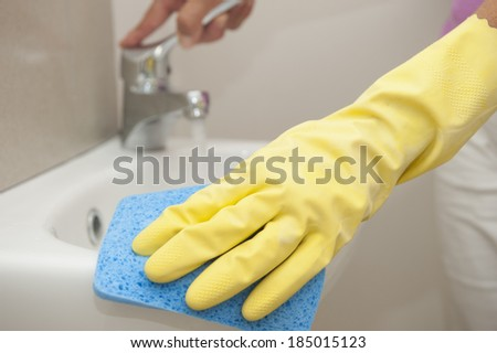 Hand in yellow rubber glove cleaning bathroom basin with blue sponge, with faucet or tap in blurred background and with copy space. - stock photo