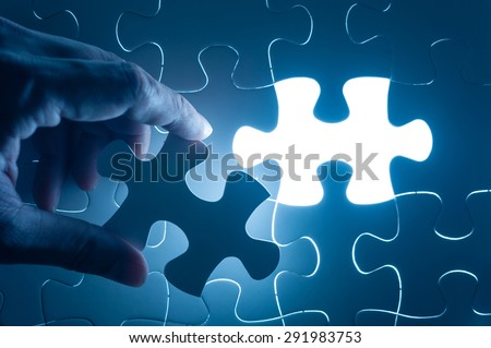 Hand insert jigsaw, conceptual image of business strategy - stock photo