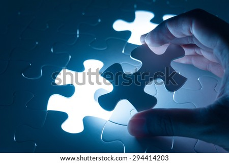 Hand insert jigsaw, conceptual image of business strategy, decision making concept - stock photo