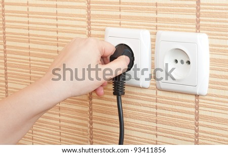 Hand insert the plug into the power - stock photo