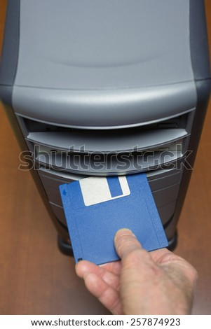 Hand inserting a 3.5-inch floppy disk into a floppy drive slot on a desktop computer. - stock photo