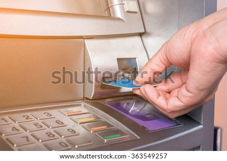 Hand inserting ATM card into bank machine to withdraw money - stock photo