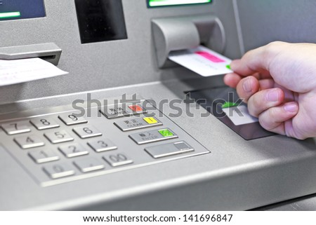 Hand inserting ATM credit card into bank machine to withdraw money - stock photo