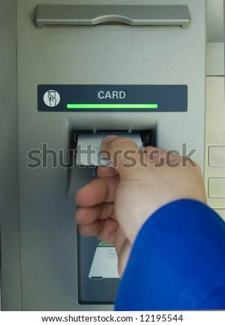 hand inserting blank card into cash machine - stock photo