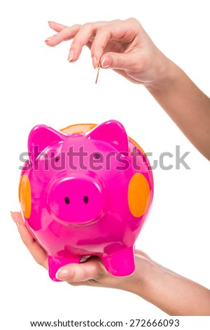 Hand inserting coin into piggy bank isolated on white background. - stock photo