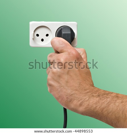 Hand inserting power plug to socket - stock photo