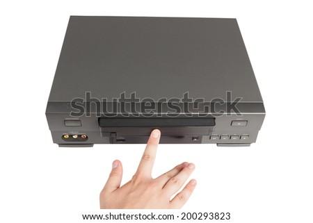 hand inserts videocassette in videorecorder - stock photo