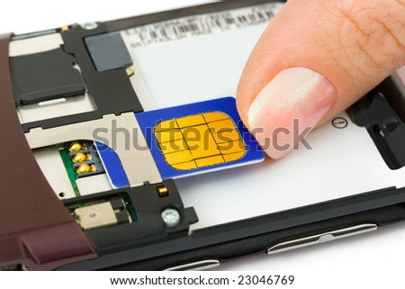 Hand install sim card to mobile phone isolated on white background - stock photo