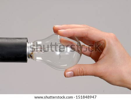 Hand installing and changing a light bulb. - stock photo